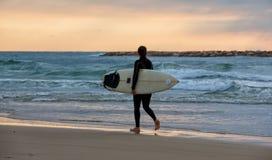 Den sportiga flickan går till att surfa Royaltyfri Bild