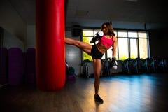 Den sportiga flickan i boxninghandskar har hans fot på påse Royaltyfri Fotografi