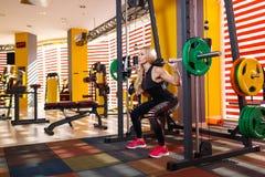 Den sportiga flickan som gör squats, övar med en tung skivstång Begreppet av sporten arkivbilder
