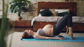 Den sportiga gravida flickan är praktiserande konditionövningar på ljus yoga som är matt i modernt vindstilsovrum Sund livsstil stock video