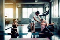 Den sportiga gruppen av kvinnayoga utbildar med instruktören i konditionidrottshall Kurs av yogaövning som exercing, stående av a royaltyfria bilder