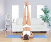Den sportiga gulliga kvinnan som kopplar av i yoga, poserar på den matta blåttövningen Royaltyfri Foto