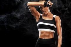 Den sportiga härliga afro--amerikanen modellen, kvinnan i sportwear gör kondition som övar på svart bakgrund för att bli färdig Royaltyfri Fotografi