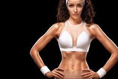 Den sportiga härliga kvinnan med lockigt hår gör kondition som övar på svart bakgrund för att bli färdig Arkivbild