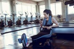 Den sportiga kvinnan använder smartphonen efter trampkvarn som övar i konditionklubba , Stående av den asiatiska kvinnan som lyss arkivfoton