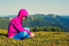 Den sportiga kvinnan, fotvandrare sitter på en grön bergäng Fotografering för Bildbyråer
