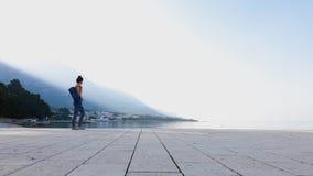 Den sportiga kvinnan går barfota på den tomma havsskeppsdockan som rymmer yoga matt lager videofilmer
