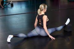 Den sportiga kvinnan gör en splittring och en sträckning royaltyfria bilder