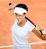 Den sportiga kvinnan håller tennisracket på henne skulder fotografering för bildbyråer