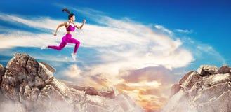 Den sportiga kvinnan hoppar till och med mellanrummet mellan kullar över himmelbakgrund arkivfoto