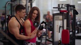 Den sportiga kvinnan lyfter hantlar, medan utarbeta i idrottshallen Hon är att försöka som är hårt, medan öva Mannen hjälper henn stock video