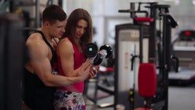 Den sportiga kvinnan lyfter hantlar, medan utarbeta i sportklubba Den idrotts- mannen hjälper henne att göra övningen korrekt arkivfilmer