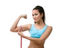 Den sportiga kvinnan mäter henne bicepen Royaltyfri Fotografi