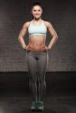 Den sportiga kvinnan med ett härligt leende, konditionkvinnlig med den muskulösa kroppen, gör hennes genomkörare, abdominals Fotografering för Bildbyråer