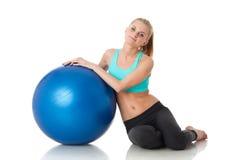 Den sportiga kvinnan med gymnastiskt klumpa ihop sig Arkivfoto