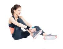 Den sportiga kvinnan sätter på hennes gymnastikskor Fotografering för Bildbyråer