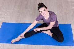 Den sportiga kvinnan som gör sträckning, övar på golvet Royaltyfri Fotografi