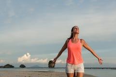 Den sportiga kvinnan som tycker om, kopplar av och frihet på stranden Royaltyfria Bilder