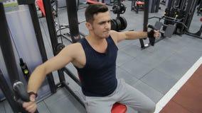 Den sportiga mannen övar i idrottshall på Pec-däcket maskinen stock video