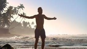 Den sportiga mannen i kortslutningar skakar händer som sträcker intensivt lager videofilmer