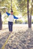 Den sportiga mannen, med den roliga framsidan, går på slackline Fotografering för Bildbyråer