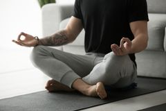 Den sportiga mannen med tatueringen som mediterar praktiserande yoga i lotusblomma, poserar Arkivbild