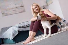 den sportiga mitt åldrades kvinnan som slår hunden, medan sitta på matt yoga royaltyfria bilder
