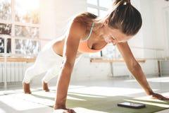 Den sportiga solbrännakvinnan som gör push-UPS på matt kondition och använder smartphonen för räkningar, resulterar i kondition a royaltyfri foto
