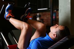Den sportiga unga mannen utarbetar ben Arkivfoto
