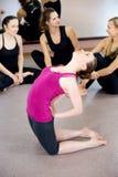 Den sportiga yogiflickan som gör yogakamlet, poserar, krökningar tillbaka i grupp Royaltyfria Bilder