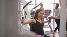 Den Sportive brunetten gör övningar i idrottshall med den personliga instruktören stock video