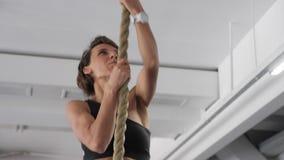 Den Sportive kvinnan klättrar på rep i idrottshall Styrkagenomkörare, sportbegrepp lager videofilmer