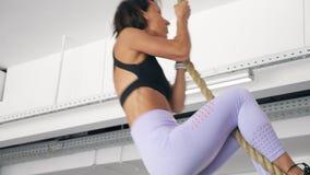 Den Sportive kvinnan klättrar på rep i idrottshall Styrkagenomkörare, sportbegrepp arkivfilmer
