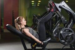 Den Sportive kvinnan som använder vikter, trycker på maskinen för ben idrottshall Fotografering för Bildbyråer