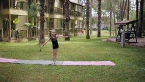 Den Sportive lilla flickan som gör en cartwheel på ängen i sommaren, parkerar lager videofilmer