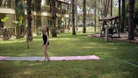 Den Sportive lilla flickan som gör en cartwheel på ängen i sommaren, parkerar stock video