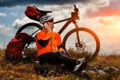 Den Sportive mannen stoppar att cykla och har en vila på dalen Royaltyfria Bilder