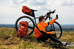 Den Sportive mannen stoppar att cykla och har en vila på dalen Royaltyfri Bild