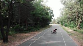 Den Sportive unga cyklistflickan i rosa dr?kt faller n?stan fr?n hennes cykel p? cykelbanan i parkerar Cykla begrepp arkivfilmer