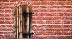 Den stängda bruna röda trädörren med rostad metall förser med gångjärn på en grungy vägg för röd tegelsten av en gammal ladugård Arkivbild