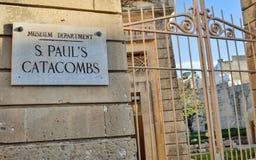Den stängda ingångsporten med tecknet till Stets Paul katakomber och museum på en sandstenvägg royaltyfria bilder