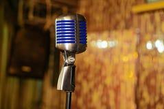 Den stängda upp retro mikrofonen är i konserthallen på bakgrunden av beröm royaltyfri foto