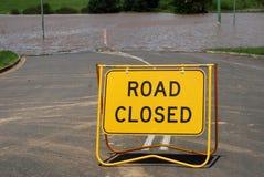 Den stängda vägen undertecknar över den översvämmade vägen Arkivbilder