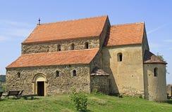 Den stärkte medeltida kyrkan av vaggar överst kullen i Cisnadioara Arkivfoton