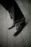 Den stå imponera manen i ett patenterat läder skor. lägger benen på ryggen endast Arkivbild