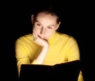 Läs- bokar glöda för ung kvinna Arkivbild