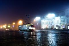 Den stads- gatan på nattetid i Europa, en spårvagn kör längs gatan Royaltyfri Bild