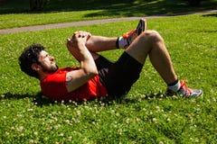 Den stads- idrottsman nen som gör sträckning, övar på gräset Royaltyfri Fotografi