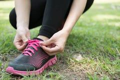 Den stads- idrottsman nenkvinnan som binder den rinnande skon, snör åt Kvinnlig sportfitne royaltyfri fotografi