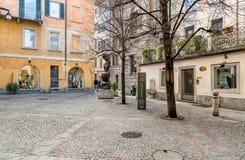 Den stads- platsen med shoppar och stänger i historisk mitt av den Varese staden Arkivbild